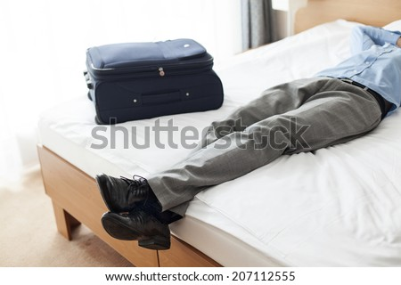 Low section of young businessman sleeping beside suitcase in hotel room - stock photo