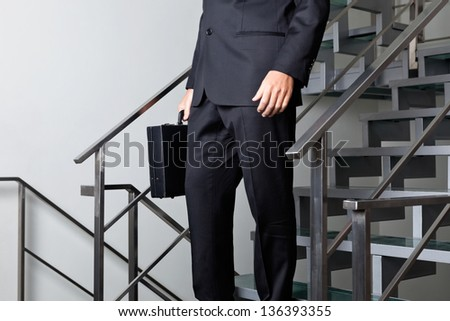 Low section of young businessman walking down the stairs at office - stock photo