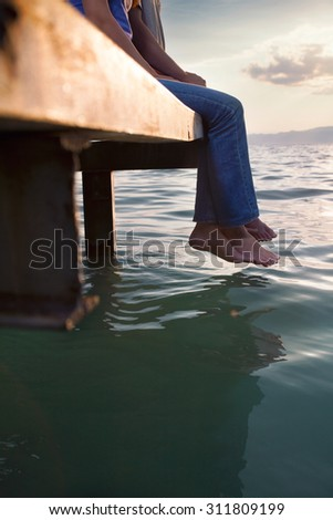 Low section of young couple sitting on the dock with their feet hanging above water - stock photo