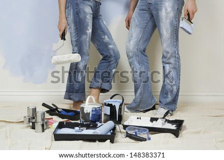 Low section of young couple standing with painting tools in foreground - stock photo