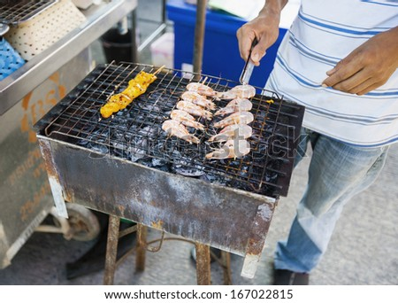Low section of young man cooking prawns on barbecue; Koh Pha Ngan; Thailand