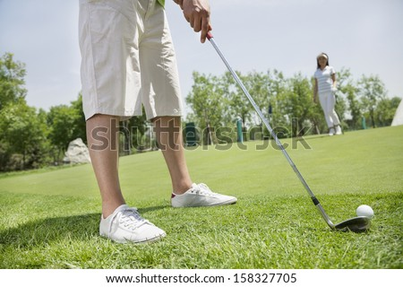 Low section of young man hitting the ball on the golf course - stock photo