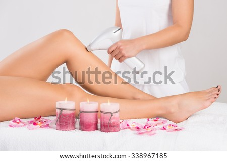 Low section of young woman getting laser treatment on leg at spa