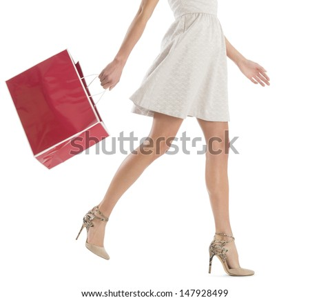Low section of young woman walking with shopping bag isolated over white background - stock photo