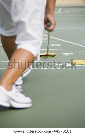 Low section view of a senior woman playing shuffleboard - stock photo