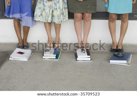 Low section view of four teenage girls standing near books in a school