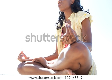 Low side body section of an african american woman in a yoga position meditating against a bright blue sky on a sunny day. - stock photo