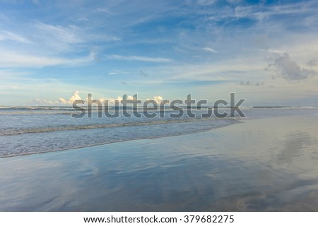 Low tide on a Beach in Central Florida where the wet fine sand reflects the sky - stock photo