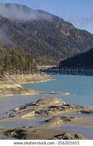 Low tide on Sylvenstein reservoir - In December 2015, the Sylvenstein Reservoir was emptied on a cleat hole due to construction work - stock photo