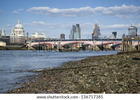 Low tide River Thames and London city skyline including St Paul's Cathedral - stock photo