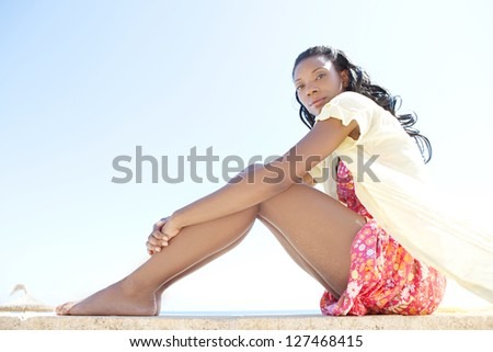 Low view of a beautiful and healthy black woman sitting against a bright blue sky on a sunny beach while on vacation. - stock photo
