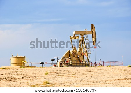 Low view of a working oil pump jack pumping crude. - stock photo