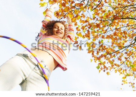 Low view of an active teenager girl playing hoola hoop in a park with orange and brown leaves on the trees, being joyful, smiling and playing during a sunny autumn day. - stock photo