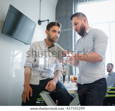 Low view of businessman explaining new business system to his colleague. Businessmen communicating about business issues or problems in office interior. - stock photo