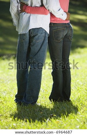 Low view of couple standing in park with arms around eachother.