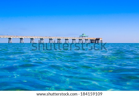Low view of fishing dock on ocean, clam water , clear blue sky.