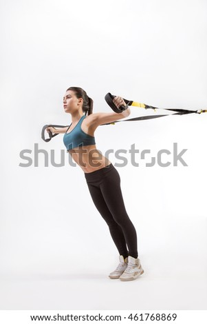 Low view of fitness trainer lady exercising on suspension trainer sling or suspension straps in studio. Upper body exercise on TRX isolated on white background.