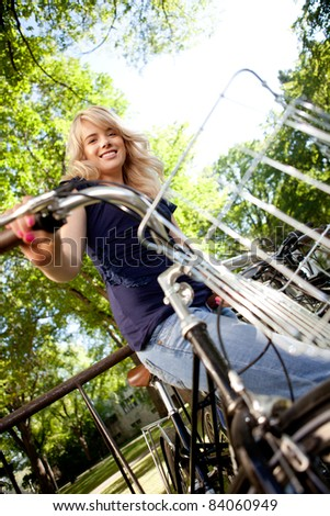 Low view of happy attractive young female with bike - stock photo