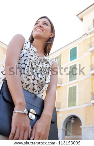 Low view portrait of a young businesswoman holding a black folder while standing in front of classic buildings in the city.