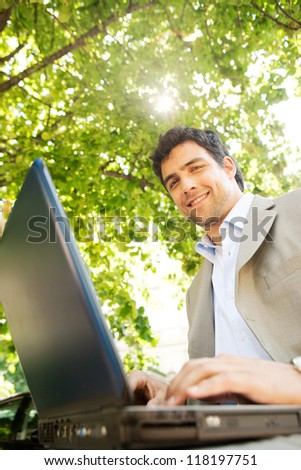 Low view portrait of an attractive young businessman using a laptop pc computer while sitting on a bench under a tree, outdoors. - stock photo