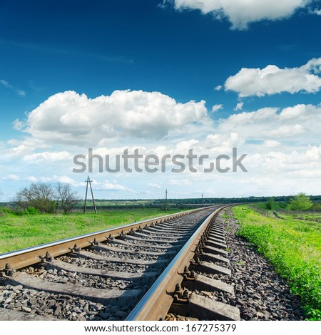 low view to railroad under cloudy sky - stock photo