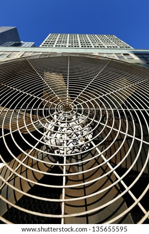 Low & wide angle close-up of an HVAC air-conditioner outdoor unit's ventilator, with a midtown NYC skyscraper rising above it on the background of clear blue sky - stock photo