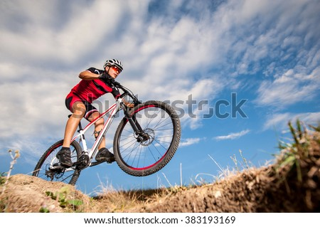 Low, wide angle portrait against blue sky of mountain biker going downhill. Cyclist in red sport equipment and helmet