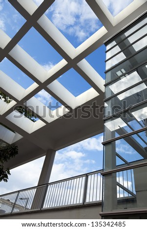 Low & wide angle view of a large pergola and a glass elevator shaft. - stock photo