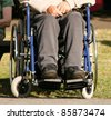 Lower body of a an elderly man sitting in a wheelchair - stock photo
