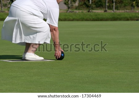 Lower body of an elderly female wearing white clothing and holding a lawn bowling ball about to bowl. - stock photo