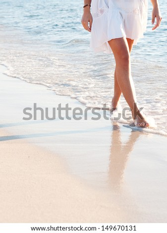 Lower body section of a young woman walking along a white sand beach shore at sunset, taking steps and relaxing in an idyllic destination during a summer vacation. - stock photo