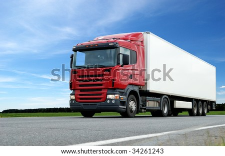 lower camera view of red lorry with white trailer on the highway over blue sky - stock photo