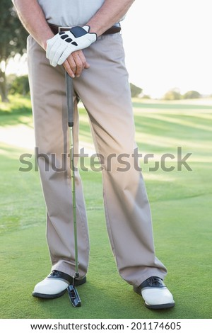 Lower half of golfer standing with club on a sunny day at the golf course - stock photo