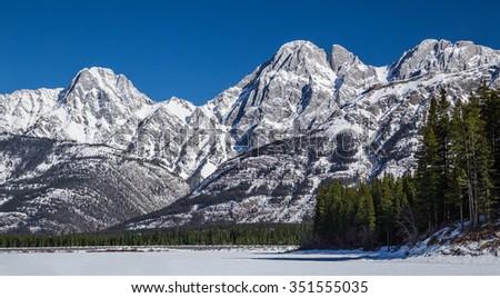Lower Kananaskis Lake, Frozen at base of mountains. Alberta, Canada - stock photo
