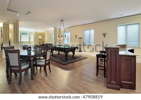 Lower level of luxury home with bar and stools - stock photo