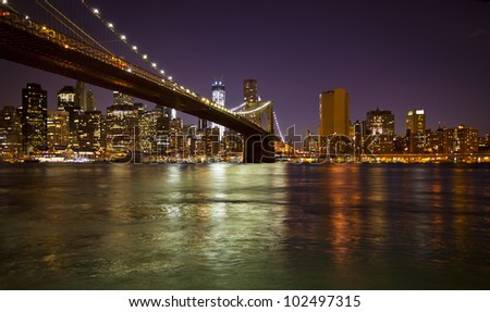 Lower Manhattan and Brooklyn Bridge in New York at nighttime - stock photo