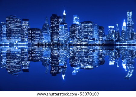 Lower Manhattan in New York City at night with reflection in water with blue hue - stock photo