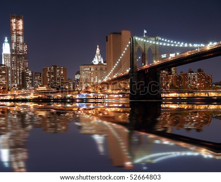 Lower Manhattan in New York City at night with reflection in water with Brooklyn Bridge