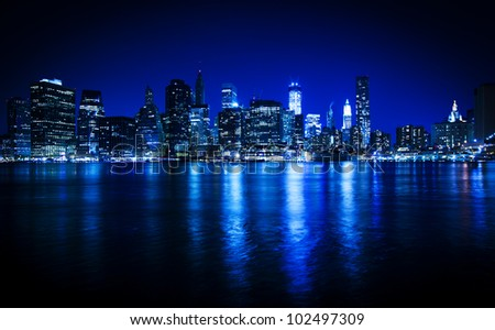 Lower Manhattan in New York in a blue hue at nighttime - stock photo