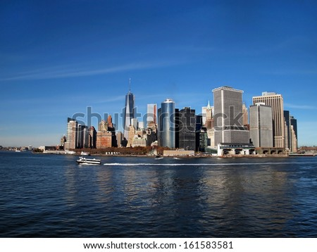 Lower Manhattan, NYC, including the new One World Trade Center Freedom Tower, can be seen across the blue water of the New York Bay at the end of the Hudson River.