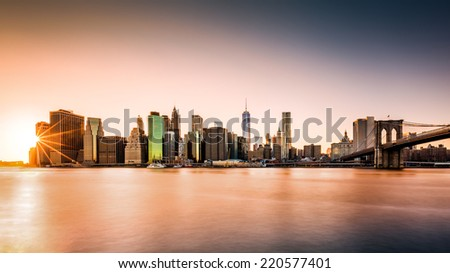Lower Manhattan skyline at sunset as viewed from Brooklyn Bridge Park - stock photo