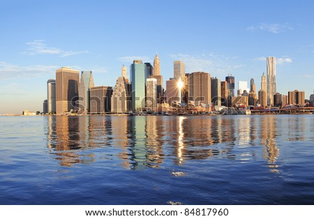 Lower Manhattan skyline panorama over East River with reflection and blue sky in New York City - stock photo