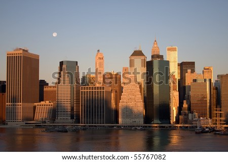 Lower Manhattan skyline viewed from Brooklyn during early morning sunrise with shadows on buildings and moon overhead