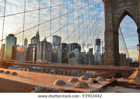 Lower Manhattan through Brooklyn Bridge at sunset,  New York City - United States - stock photo