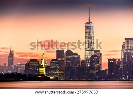 Lower Manhattan with Freedom Tower and The Statue of Liberty at sunrise - stock photo