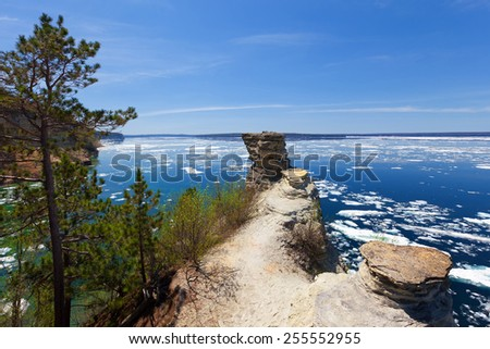 Lower overlook at Miners Castle on the shores of Lake Superior located at Pictured Rocks National Lakeshore. Ice floes appear on Lake Superior due to a spring breakup of ice. - stock photo