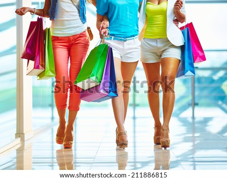 Lower part of beautiful shopaholics with paperbags walking down trade center - stock photo