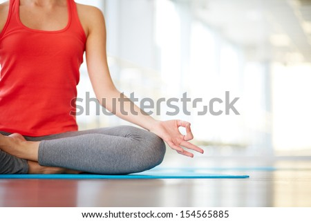 Lower part of slim female meditating in pose of lotus in gym - stock photo