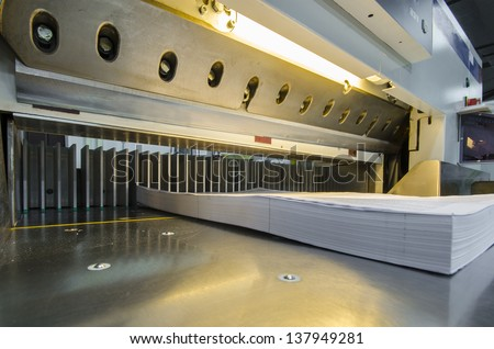 Lower view of a modern paper guillotine with touch screen used in commercial printing industry (industrial knife cutter) - stock photo