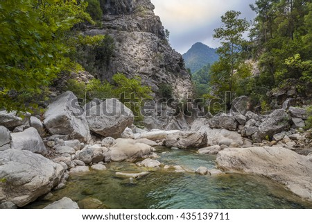 Lower view of mountain stony river, rocks, trees, stones and sky in Goynuk canyon in Turkey
